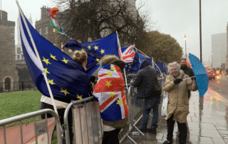 Brexit protesters standing outside on a rainy UK street